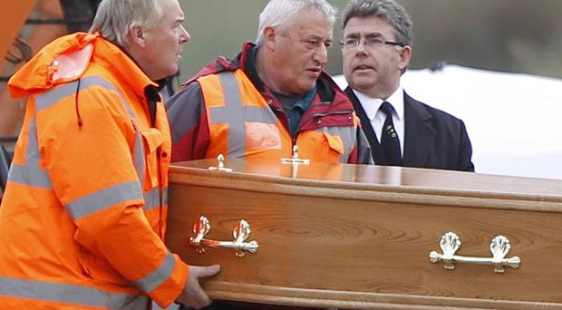 The remains of a body, believed to be that of 'Disappeared' victim Peter Wilson, are removed from a beach. The body of another victim has been identified as that of Gerry Evans