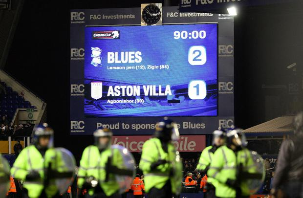 General view of the final score on the scoreboard as riot Police line up on the pitch after Birmingham City fans invade the pitch during the Carling Cup, Quarter Final match at St Andrews, Birmingham. PRESS ASSOCIATION Photo. Picture date: Wednesday December 1, 2010. See PA story SOCCER Birmingham. Photo credit should read: Nick Potts/PA Wire. RESTRICTIONS: Use subject to restrictions. Editorial print use only except with prior written approval. New media use requires licence from Football DataCo Ltd. Call +44 (0)1158 447447 or see www.pressassociation.com/images/restrictions for full restrictions.