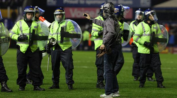 A Birmingham City fan films the Riot Police on his phone as they push back the Birmingham fans who invaded the itch at full time during the Carling Cup, Quarter Final match at St Andrews, Birmingham. PRESS ASSOCIATION Photo. Picture date: Wednesday December 1, 2010. See PA story SOCCER Birmingham. Photo credit should read: Nick Potts/PA Wire. RESTRICTIONS: Use subject to restrictions. Editorial print use only except with prior written approval. New media use requires licence from Football DataCo Ltd. Call +44 (0)1158 447447 or see www.pressassociation.com/images/restrictions for full restrictions.