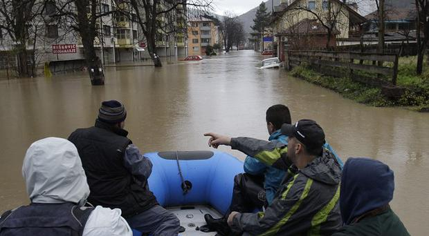 Rescuers bring food and drinking water to citizens trapped in houses flooded with water from the river Drina, in Gorazde, Bosnia (AP)