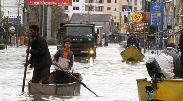 People in boats move through the floodwater in Albania (AP)