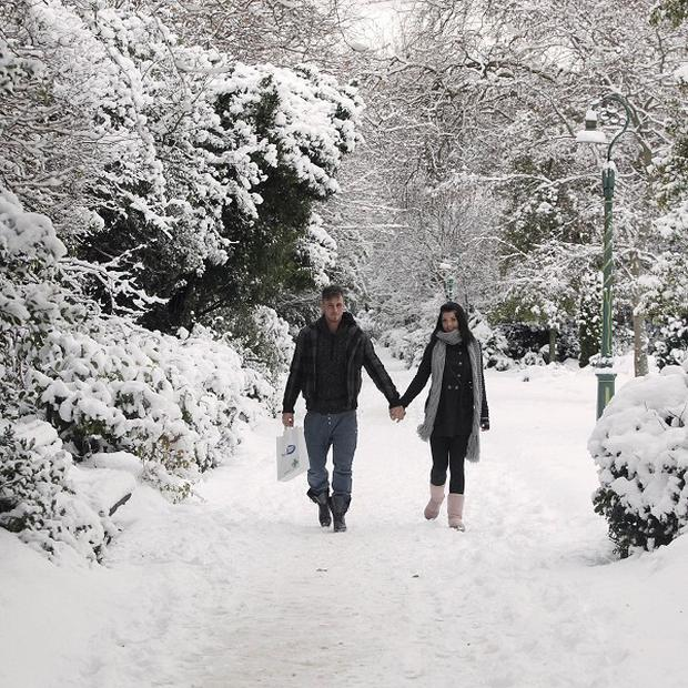 A couple walk in the snow in Dublin's Merrion Square after another night of heavy snow in the capital