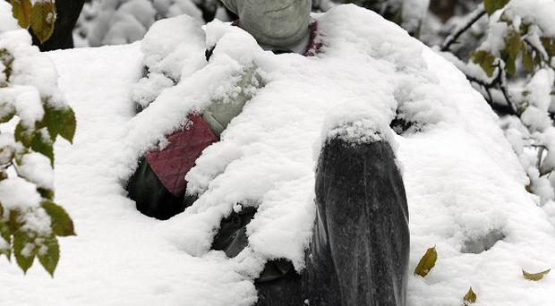 A statue of Oscar Wilde covered in snow in Dublin's Merrion Square