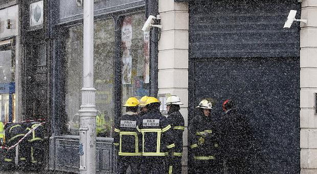 Gardai and Firemen on O'Connell Street outside The Kylemore Cafe