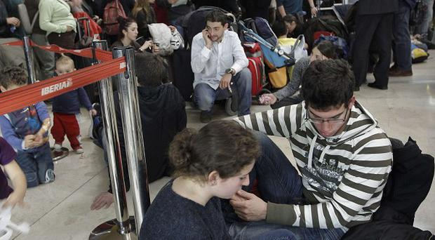 Passengers wait for news about their flights at T4 terminal of Barajas airport in Madrid