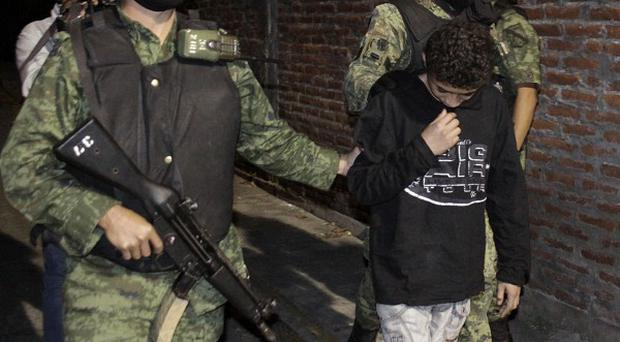 Mexican army soldiers escort a 14-year-old suspected of working as a killer for a drug cartel (AP)