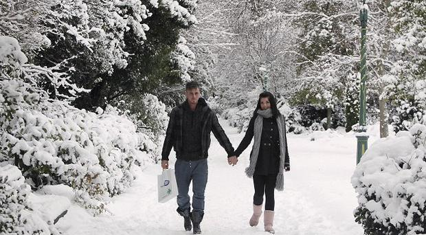 A couple walk in the snow in Dublin's Merrion Square