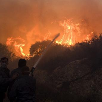 Firefighters try to extinguish the flames in Tirat Hacarmel, northern Israel (AP)