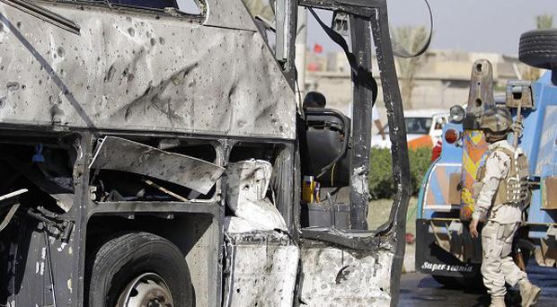 An Iraqi army soldier inspects a destroyed bus in Baghdad which was carrying Iranian pilgrims (AP)