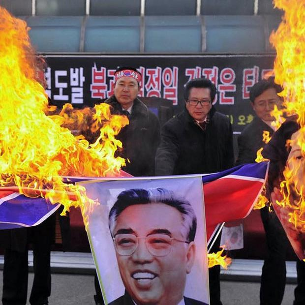 South Korean military veterans burn a North Korean flag and portrait of Kim Il Sung, the late founder of North Korea. (AP)