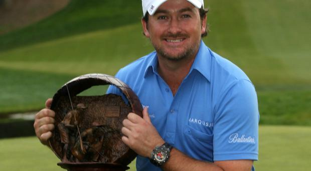Graeme McDowell shows off his trophy following last night's thrilling victory over Tiger Woods in the Chevron World Challenge, which went to a play-off