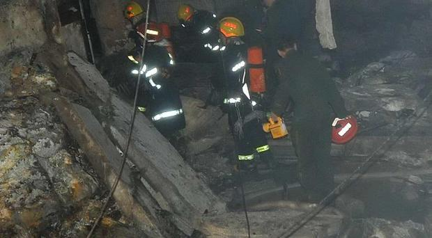 Firefighters enter the wreckage of an internet cafe in south-west China after an explosion (AP)