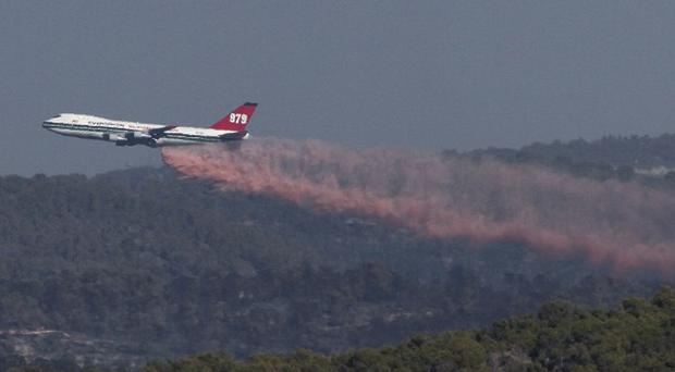 A jumbo jet is used to spray fire extinguishing material over the blaze (AP)