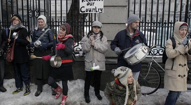 Demonstrators bang pots and pans outside Leinster House in Dublin in protest against the Government's austerity budget