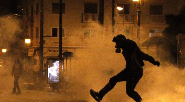 A protester kicks a gas canister back at riot police in Athens (AP)