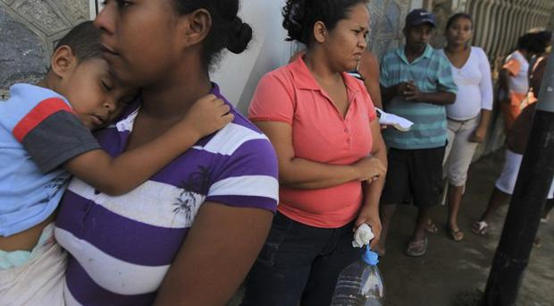 Flood victims line up for food and water outside a fire station in Higuerote, central Venezuela