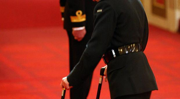 Corporal Ricky Furgusson, The Rifles, walks up to the stage to be decorated with the Military Cross, for services in Afghanistan