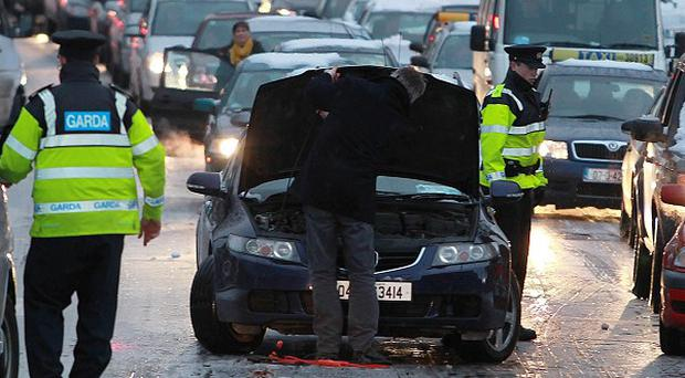 Gardai help motorists deal with icy roads along North Strand during rush hour in central Dublin