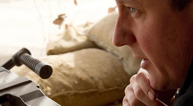 David Cameron surveys a nearby village from the top of a sangar observation point in Helmand Province