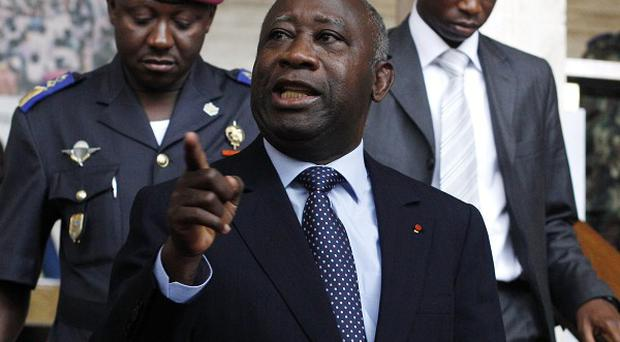 Laurent Gbagbo gestures as he walks between meetings ahead of naming his new cabinet in Abidjan, Ivory Coast