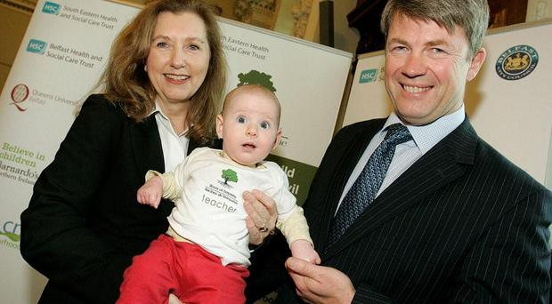 Baby teacher Tess Gillen held up by Mary Gordon, founder of Roots of Empathy and Hugh McCaughey chief executive, South Eastern Health Trust