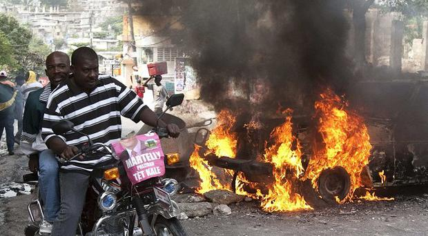 Supporters of presidential candidate Michel Martelly ride past a burning barricade during protests in Port-au-Prince