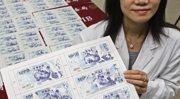 Liu Hui-fen displays pages of thousands of tiny pieces of note bills that she patched together (AP)