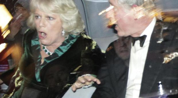 Prince Charles and the Duchess of Cornwall react as their car is attacked by fees protesters