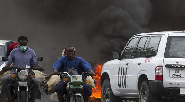 A UN vehicle approaches a burning barricade in Port-au-Prince, Haiti