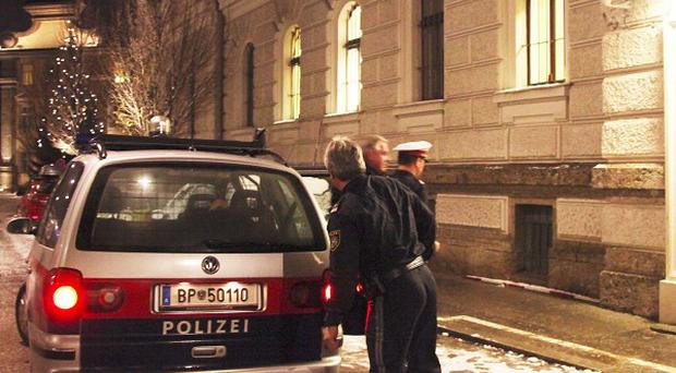 Former Croatian Prime Minister Ivo Sanader is escorted from a police car in front of a courthouse in Salzburg