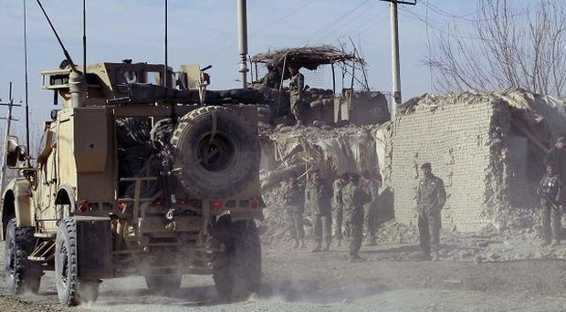 A US military vehicle passes by a damaged military check post after a suicide attack in Kunduz, north of Kabul, Afghanistan(AP)