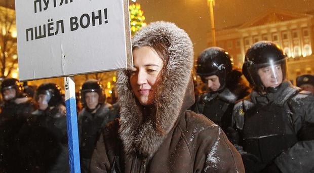 A woman holds a banner saying 'Putin go away!' during a rally in central Moscow (AP)