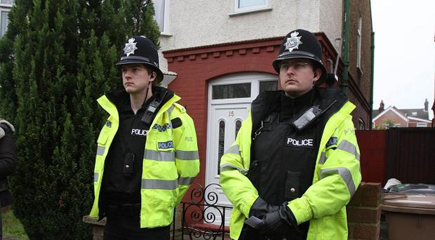 Police officers stand outside a property on Argyll Avenue in Luton allegedly linked to the Sweden bombings