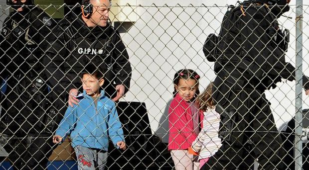 Elite gendarme officers release children from a school, after an hostage taking in Besancon, eastern France (AP)