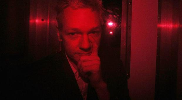 Wikileaks founder Julian Assange gestures inside a prison van with red windows as he leaves Westminster Magistrates Court on December 14, 2010 in London, England