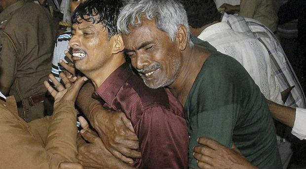The relatives of victims of an accident cry on the outskirts of Mysore, India