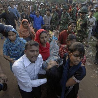 Rescuers carry a victim of a factory fire in Ashulia, north of the capital Dhaka, Bangladesh (AP)