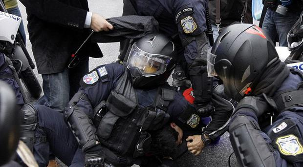 Police arrest a protester during clashes in Athens (AP)