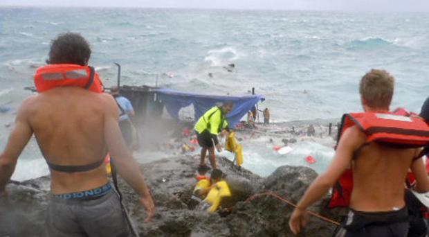 A wooden boat packed with asylum seekers smashed apart on rocks off Christmas Island (AP)