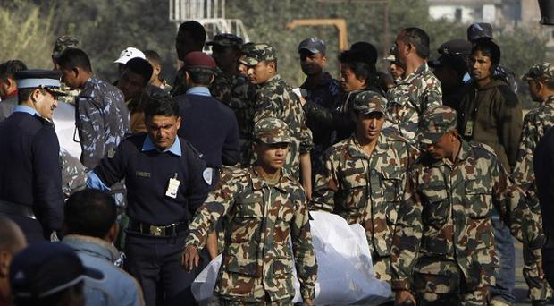 Nepalese soldiers carry the remains of a plane crash victim in Kathmandu (AP)