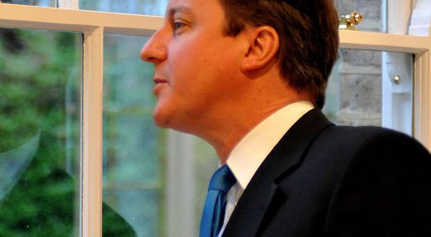 Prime Minister David Cameron inspects energy-efficient windows during a visit to Building Research Estate
