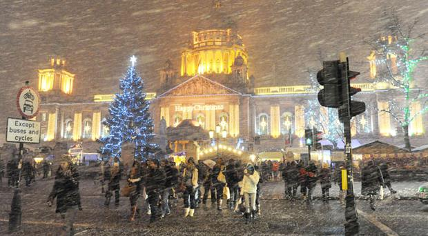Christmas shoppers battle through a heavy snow storm in Belfast city centre