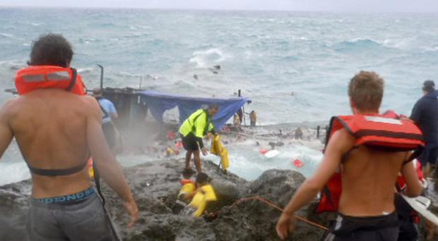 People clamber on the rocky shore on Christmas Island during a rescue attempt as a boat breaks up
