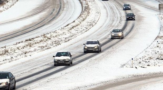 Cars negotiate the M22 outside Ballymena, Co Antrim, amid severe weather