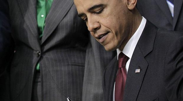 US president Barack Obama signs a tax deal into law in the White House (AP)