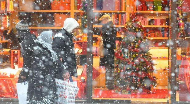 Christmas shoppers in London's West End brave the snow as winter weather returns to the capital
