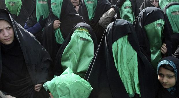 Covering their faces with green niqabs, Iranian women perform Tazieh, a traditional theater scene about Imam Hussein, a grandson of Prophet Muhammad (AP)