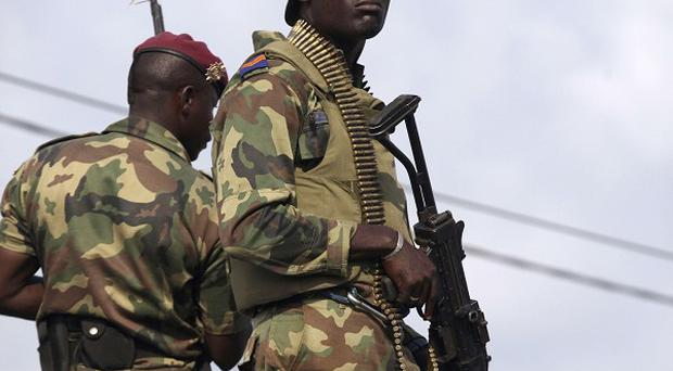 Ivory Coast soldiers stand guard during a youth rally in Abidjan