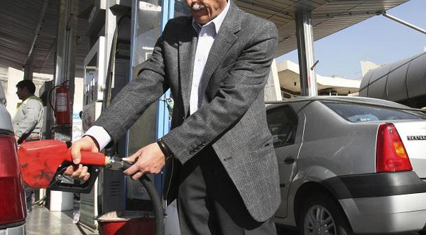Iranians fill their vehicles in a petrol station in central Tehran, after Iran's president announced the start of a plan to slash energy and food subsidies (AP)