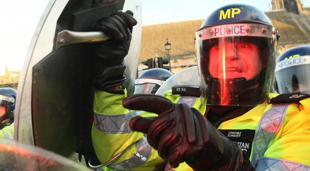 Riot police hold back demonstrators in Parliament Square, as students demonstrate against planned tuition fee increases